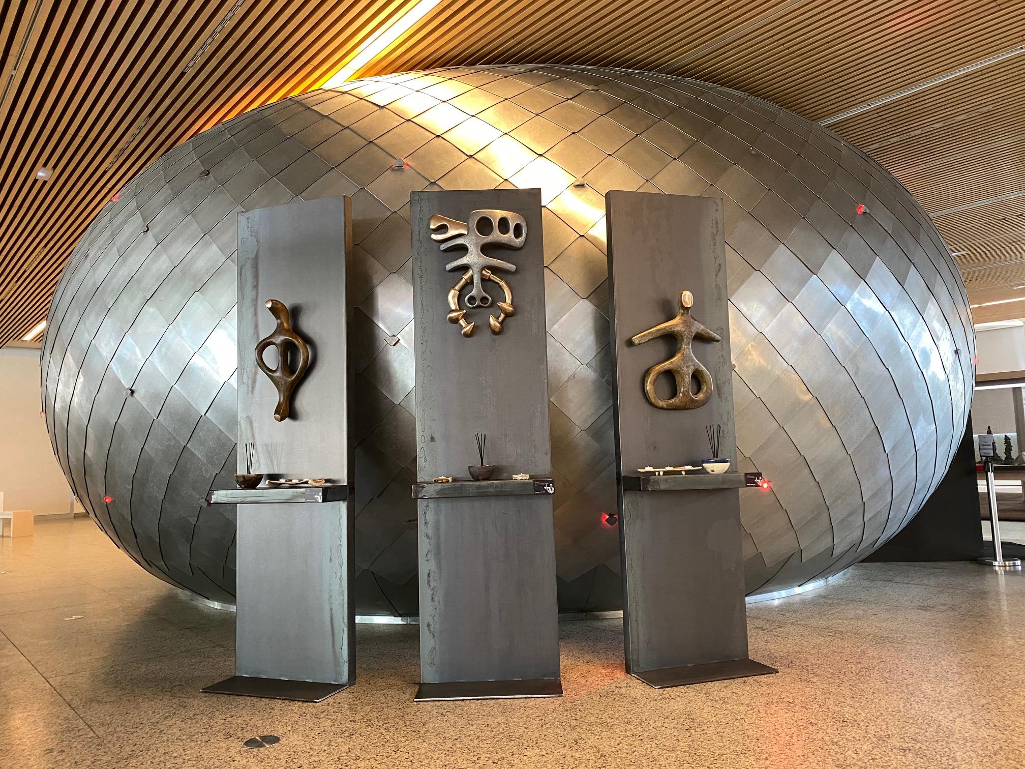 Lu par les déficiants visuels. Décrire l'image : sculpture en bronze représentant des symboles féminins, sur fond de ... réalisés par l'artiste NOM et présenté par la galerie d'art 3838 à Angers